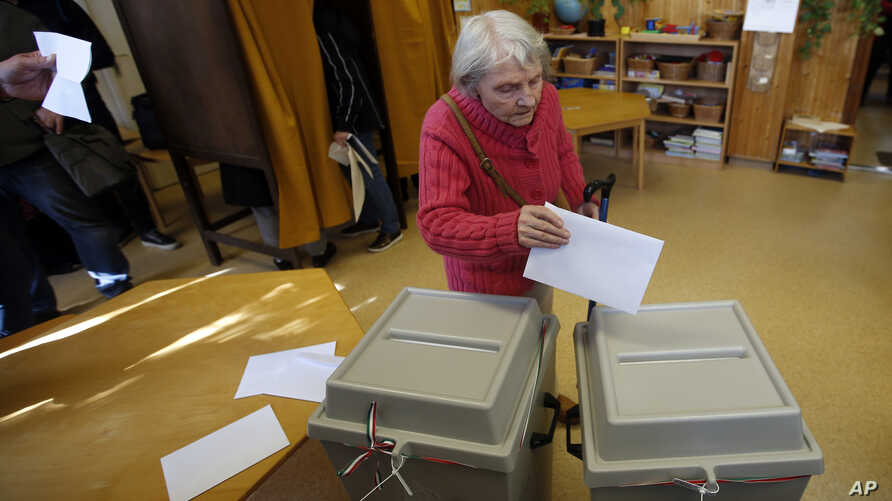 A voter casts her ballot at a polling station in Budapest, Hungary, Sunday, April 8, 2018. Orban is expected to win his third consecutive term, and fourth overall since 1998, as voting stations opened across the country for the election of 199 parlia