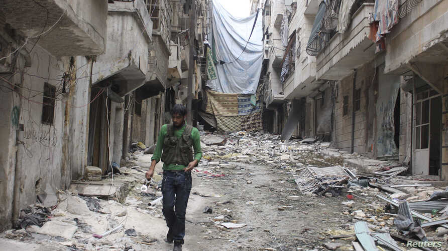A Free Syrian Army fighter carries handcuffs as he walks along the rubble of damaged buildings in Aleppo's Salaheddine neighborhood, Nov. 7, 2013.
