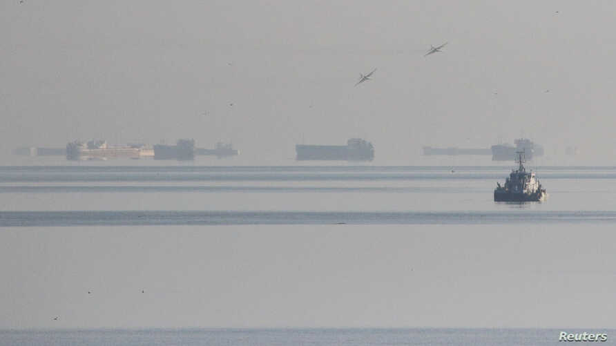 Russian fighter jets fly over vessels after the channel beneath a bridge connecting the Russian mainland with the Crimean peninsula was blocked to stop three Ukrainian navy ships from entering the Sea of Azov, Nov. 25, 2018.