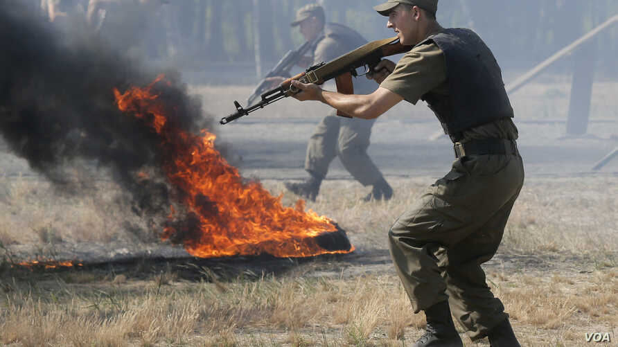 Ukrainian soldiers demonstrate their skills prior to being sent to the country's east to fight against pro-Russian separatists at a base near Kiev July 22, 2015.