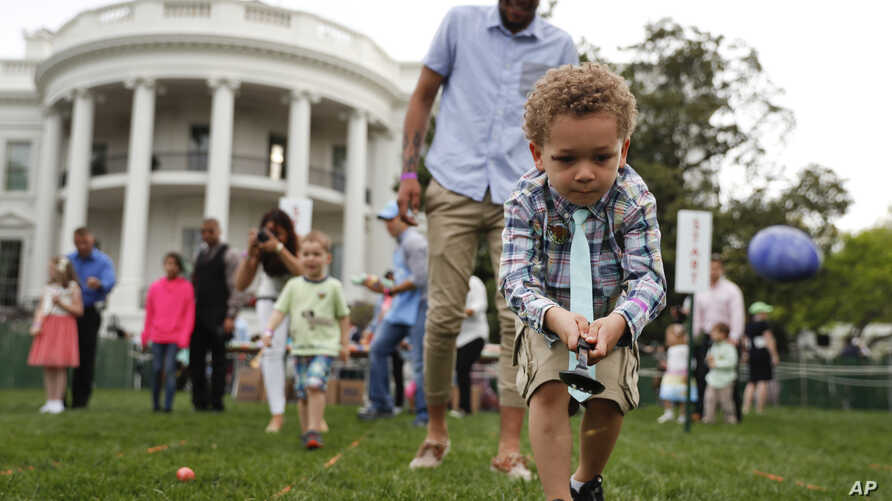 FILE - Eggs fly as children get a little help from parents to cross the finish line during the White House Easter Egg Roll on the South Lawn of the White House in Washington, April 17, 2017, hosted by President Donald Trump and first lady Melania Tru
