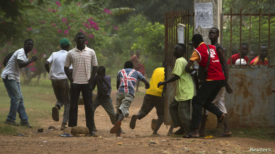 A crowd runs for cover as African Union (AU) peacekeeping soldiers fire warning shots to disperse a crowd near the district of Miskine in Bangui, Feb. 7, 2014.