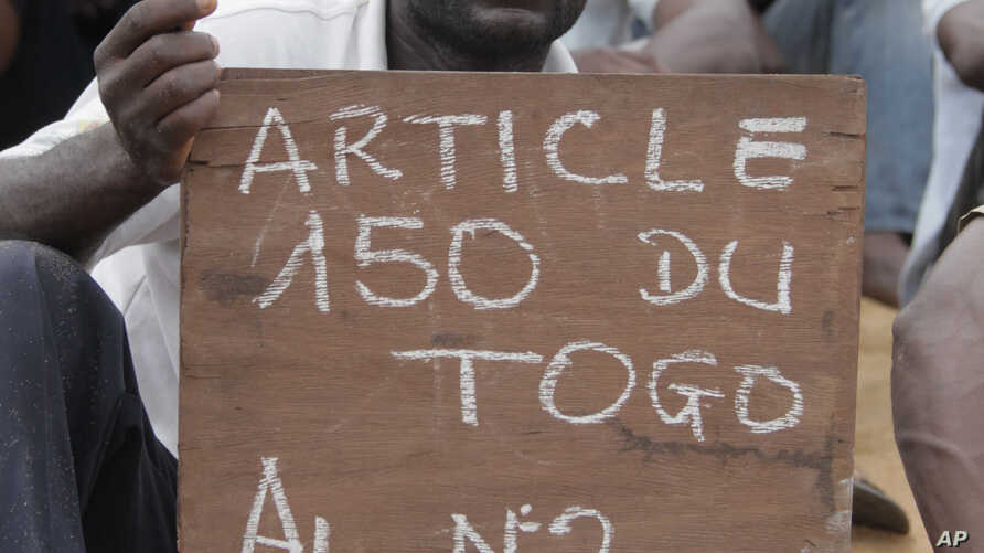 An opposition protestor holds a sign reading 'Faure, Resign,' referring to Togo's president, Faure Gnassingbe, and citing an article of the constitution that protesters say gives them the right to engage in civil disobedience, during an opposition si