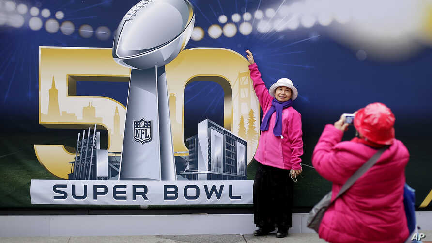 Angie Bagares poses for a photo in front of a Super Bowl 50 sign at Super Bowl City in San Francisco, Feb. 3, 2016.