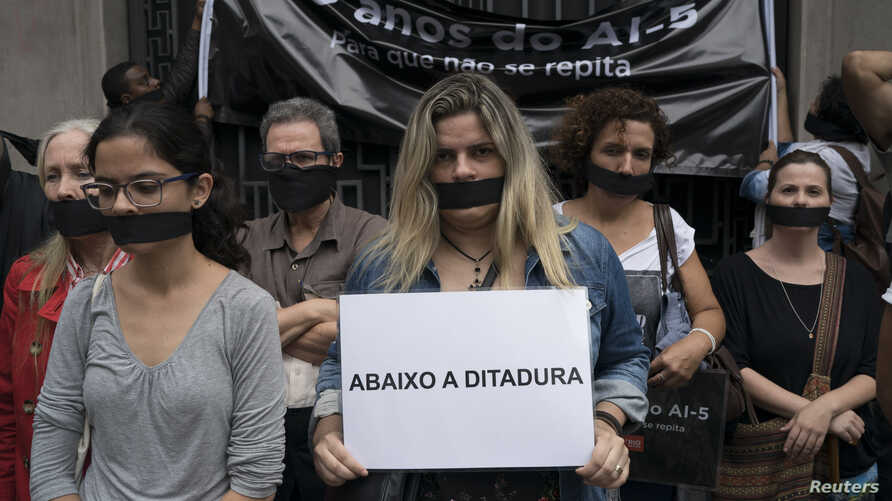 """Wearing a gag over her mouth, a woman holds a sign that reads in Portuguese """"Down the dictatorship"""" during an act organized by the NGO Rio de Paz to remember the victims of Brazil's dictatorship, in Rio de Janeiro, Brazil, Dec. 8, 2018."""