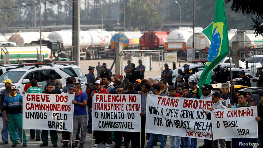 """Truck owners block the main entrance of the gasoline and gas terminal in Barueri, Brazil, May 23, 2018. Signs reads """"Strike of the truckers united by Brazil."""""""