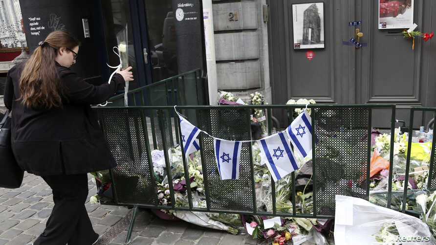 A passer-by places flowers at the entrance of the Jewish Museum in Brussels, Belgium, May 27, 2014.