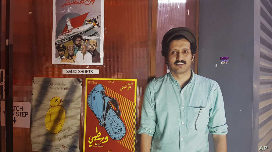 """In this Aug. 25, 2017 photo, Saudi filmmaker Ali Kalthami stands next to the poster for his film """"Wasati"""" or """"Moderate"""" and two other Saudi short films recently shown at Cinema Akil in Dubai, United Arab Emirates."""