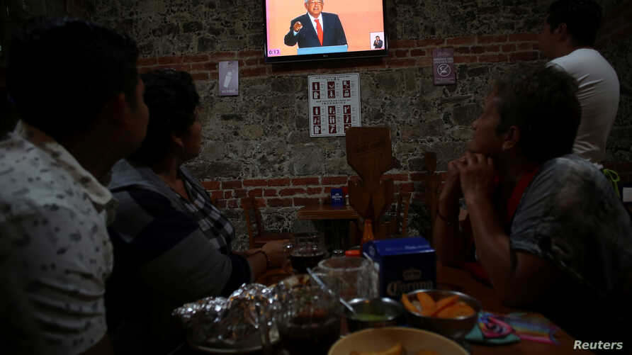 Clients watch leftist front-runner Andres Manuel Lopez Obrador, of the National Regeneration Movement (MORENA), on TV during the transmission of the first presidential debate at a restaurant in Mexico City, April 22, 2018.