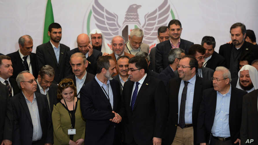 Syrian opposition chairman Sheikh Moaz Al-Khatib (center, left) chats with the Coalition's newly elected interim prime minister, Ghassan Hitto (center right), as other coalition members look on at the end of a long one-day election Monday night in Is