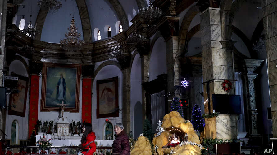 Chinese women walk past a decoration displaying a Baby Jesus doll part of a Nativity scene, at the Nantang Catholic Church in Beijing, Dec. 28, 2016.