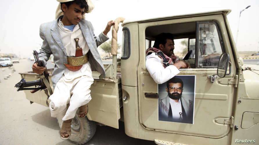 An image of al-Houthi Hussein Badr Eddin al-Huthi, the late founder of Yemen's al-Houthi Shi'ite group, is seen on a vehicle as his follower jumps from it while carrying a weapon to secure a road in the northwestern province of Saada, June 4, 2013.
