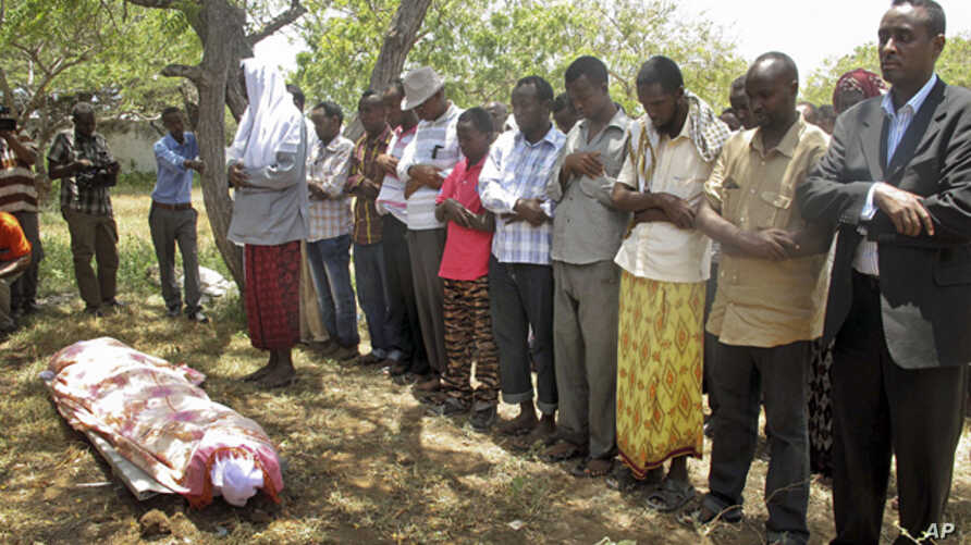 Friends and relatives of Abdisatar Dahir Sabriye, a well known journalist with state-run television who died in Thursday's suicide bomb attack, attend his funeral in Mogadishu, Sept. 21, 2012.