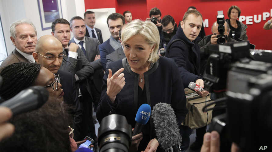 FILE - French far-right leader and presidential candidate Marine le Pen answers reporters questions at her campaign headquarters, Nov.16, 2016, in Paris.