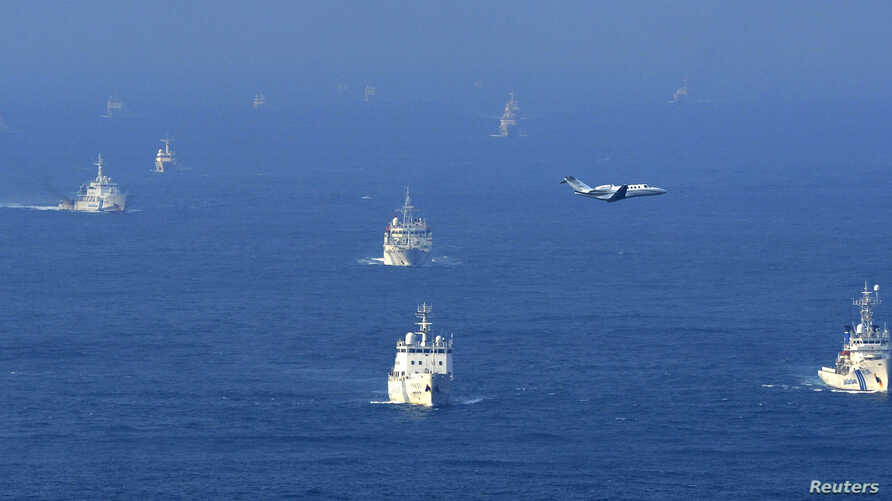 An aerial photo from Kyodo News shows Chinese ocean surveillance, fishery patrol ships and a Japan Coast Guard patrol ship (R and 2nd L) sailing about 27 km (17 miles) west from a group of disputed islands, known as Senkaku in Japan and Diaoyu in Chi
