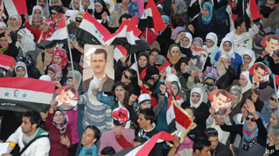 Supporters of Syria's President Bashar al-Assad shout slogans in Syria's northern city of Aleppo, March 27, 2011