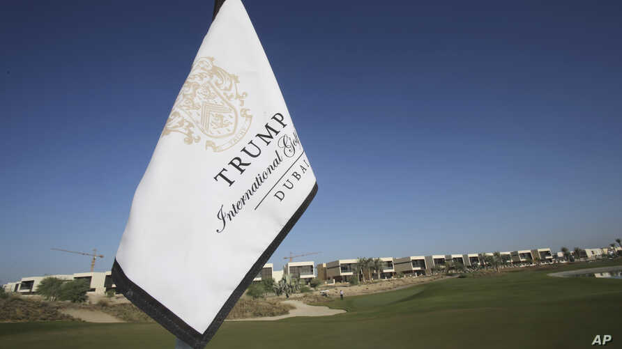 In this Tuesday, Dec. 20, 2016 photo, a flag flies on a green lined with villas at the Trump International Golf Club, in Dubai, United Arab Emirates.