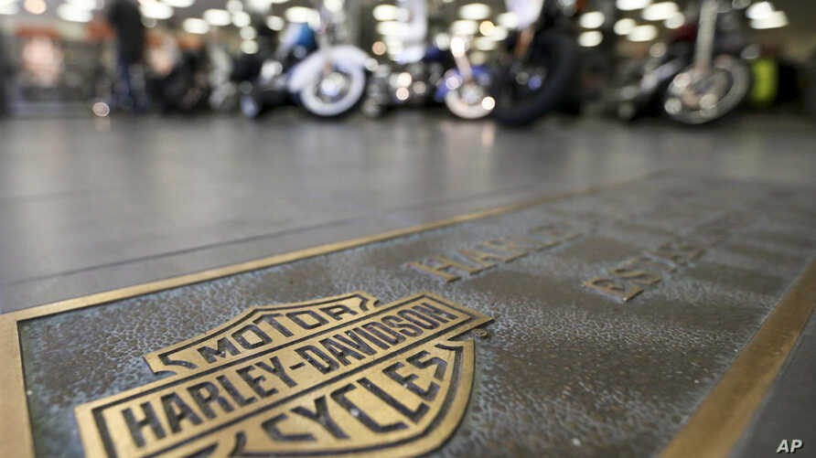 FILE - Rows of motorcycles are seen behind a bronze plate with corporate information on the showroom floor at a Harley-Davidson dealership in Glenshaw, Pennsylvania, April 26, 2017.