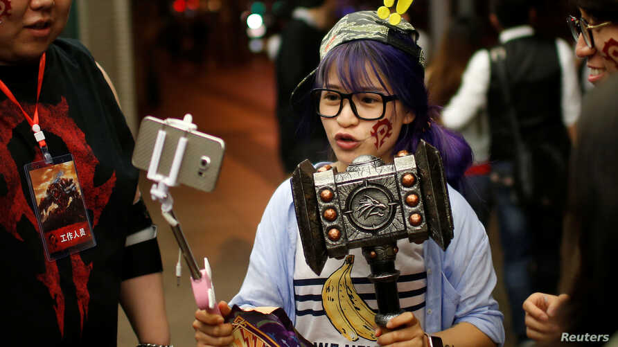 """A fan livestreams her participation during China's premiere of the film """"Warcraft"""" at a theater in Shanghai, China, June 7, 2016."""