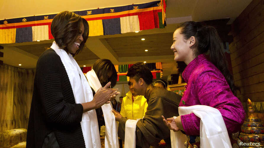 U.S. First Lady Michelle Obama, her daughters Sasha, Malia, and mother Marian Robinson are greeted with a Khata scarf by Tibetan students as they arrive to a Tibetan restaurant for lunch in Chengdu in southwest China's Sichuan province, March 26, 201