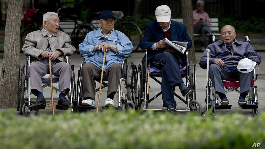 A group of elderly men take a rest on their wheelchairs at a park in Beijing, (File photo).