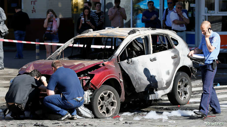 Investigators inspect a damaged car at the site where journalist Pavel Sheremet was killed by a car bomb in central Kyiv, Ukraine, July 20, 2016.