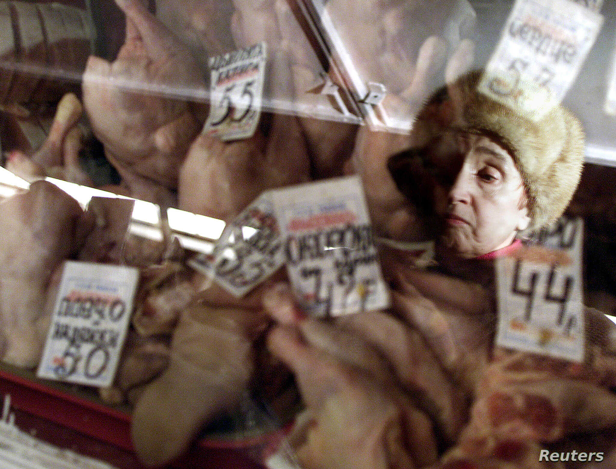 FILE - A Russian woman is reflected in the glass as she looks at poultry at a market in Moscow.