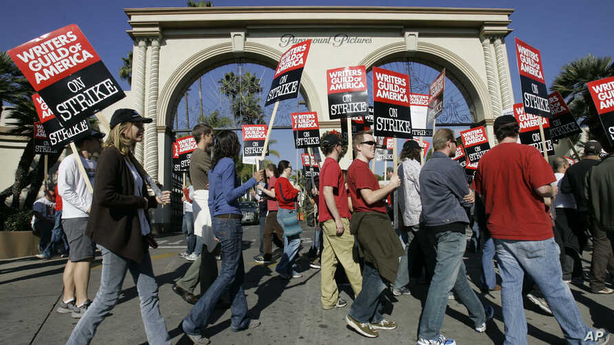 FILE - striking writers walk the picket line outside Paramount Studios in Los Angeles.