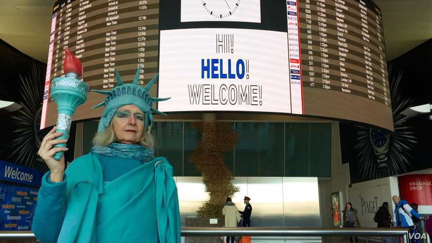 "Lindley Hanlon, a film professor at CUNY, spent Monday afternoon at JFK international airport to welcome refugees. ""I'm trying to welcome people to our shores, as I've always done for 131 years,"" she said, referring to Lady Liberty's arrival in New Y"