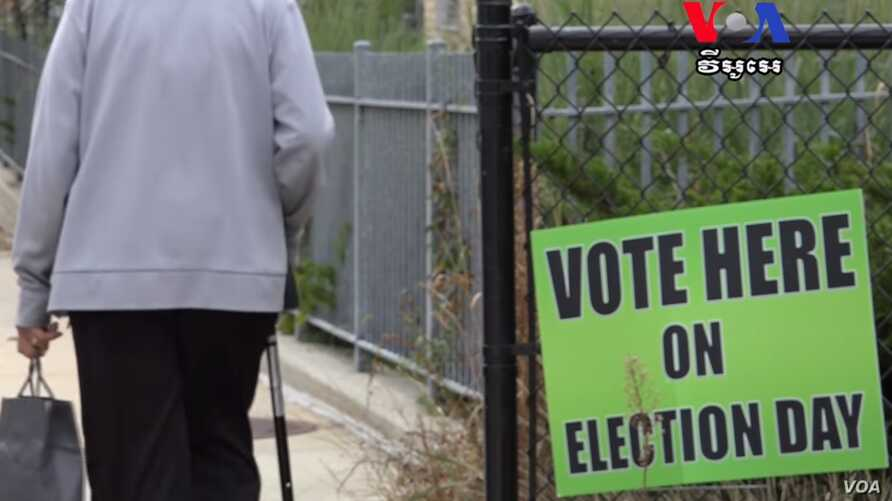 An elder walks pass the voting sign placed on the fence at one of the public schools in Lowell, on Thursday, September 8, 2016.