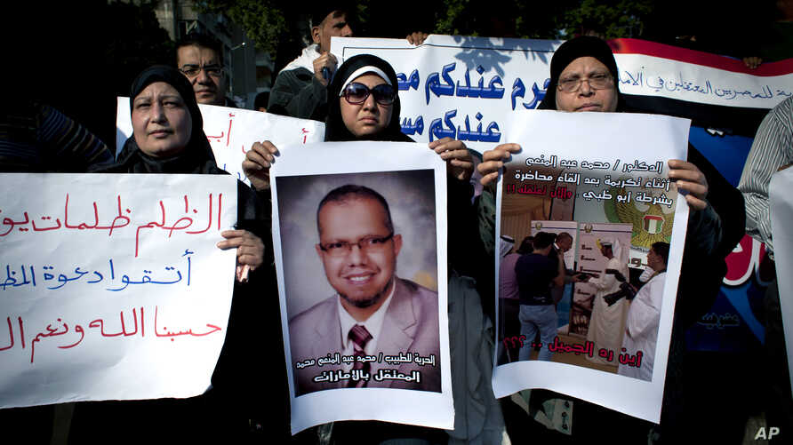 """Muslim Brotherhood supporter carries a banner, center, in Arabic that reads, """"freedom to doctor Mohammed Abdel Monem, arrested in the United Arab Emirates,"""" during an ongoing protest in front of the United Arab Emirates embassy, unseen, in Cairo, Egy"""
