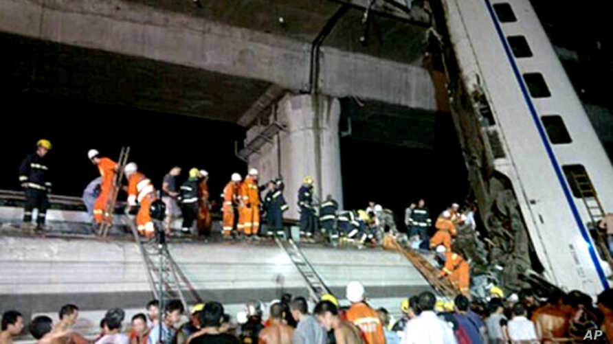 Chinese firefighters work to rescue survivors after a Chinese high-speed train derailed and two of its carriages fell off a bridge after a lightning strike knocked out power on the line in China's Zhejiang province, July 23, 2011