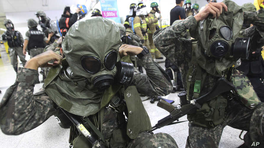 """South Korean army soldiers put on gas masks during South Korea-U.S. joint military exercise, """"Ulchi Focus Lens,"""" at a subway station in Seoul, South Korea, Aug. 19, 2013."""