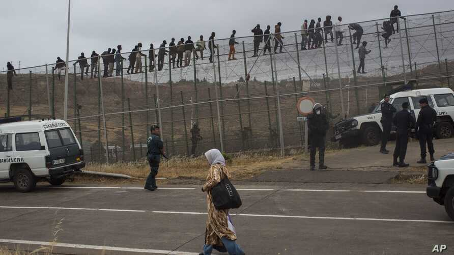 FILE - A woman walks past Sub-Saharan migrants sitting on top of a metallic fence that divides Morocco and the Spanish enclave of Melilla, May 17,  2014.