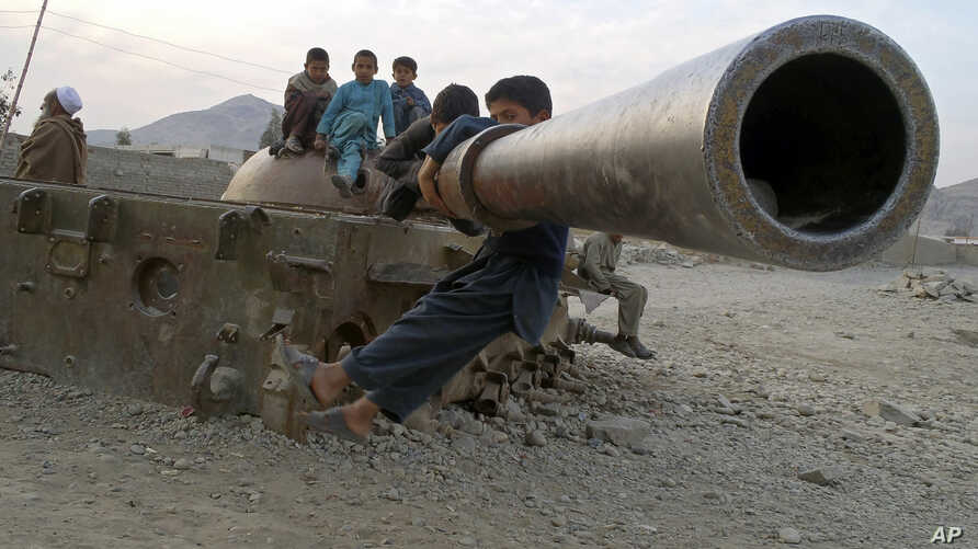 Afghan children play on the remains of a Soviet tank in the Behsood district of Jalalabad, Afghanistan, Feb 18, 2013.