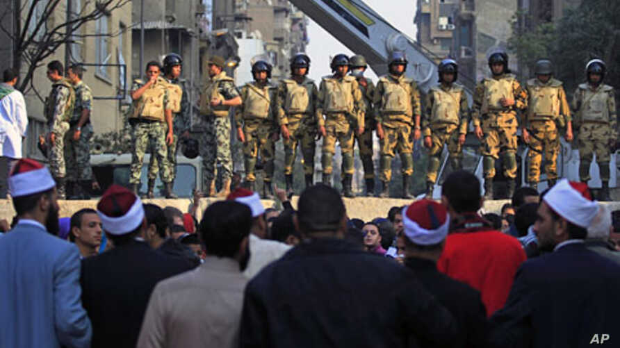 Egyptian Army soldiers stand guard atop a concrete block barricade on the street between Tahrir Square and the interior ministry in Cairo, Egypt, Nov. 24, 2011