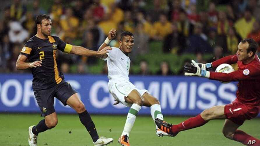 Australia's goalkeeper Mark Schwarzer (R) saves a strike from Saudi Arabia's Naif Ahmed Hazazi (C) as Australia's Lucas Neill watches during their World Cup qualifier soccer match at AAMI Park in Melbourne, February 29, 2012.