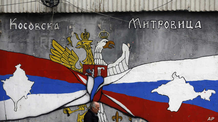 A man walks by graffiti that shows Serbian, left, and Russian flags with maps of Kosovo and Crimea in northern, Serb-dominated part of ethnically divided town of Mitrovica, Kosovo, Dec. 15, 2018. Serbia threatened a possible armed intervention in Kos