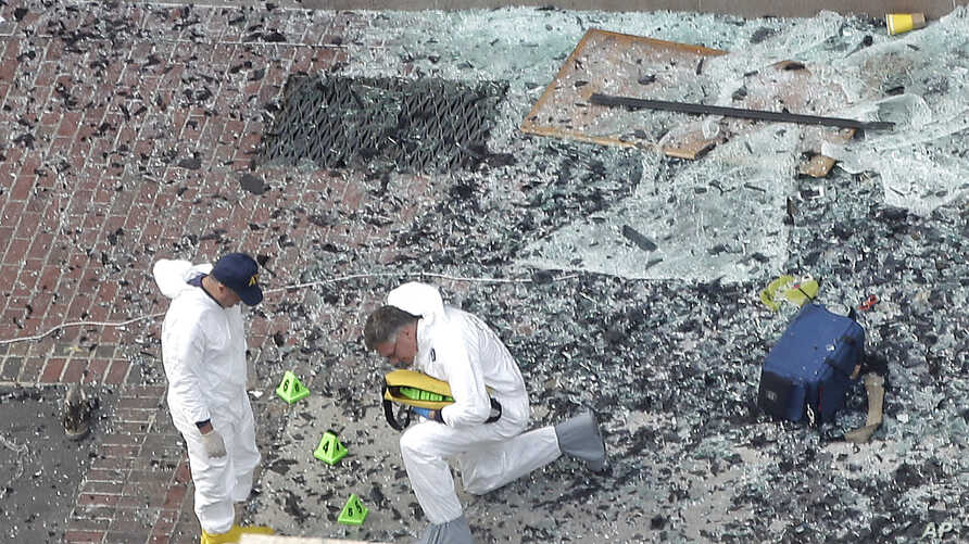 Boston Marathon ExplosionsTwo men in hazardous materials suits put numbers on the shattered glass and debris as they investigate the scene at the first bombing on Boylston Street near the finish line of the 2013 Boston Marathon, a day after two blast