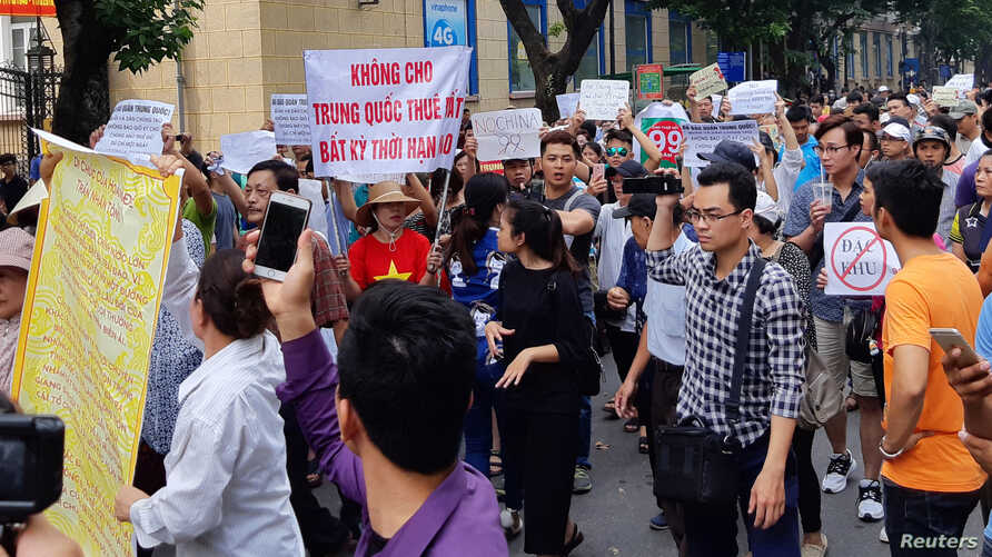 "Protesters hold a banner which reads ""No Leasing Land to China even for Anytime"" during a demonstration against a draft law on the Special Economic Zone in Hanoi, Vietnam, June 10, 2018."