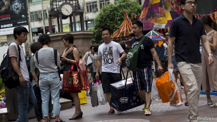 Chinese tourists carry shopping bags in Hong Kong's Causeway Bay shopping district, Sept. 21, 2015.