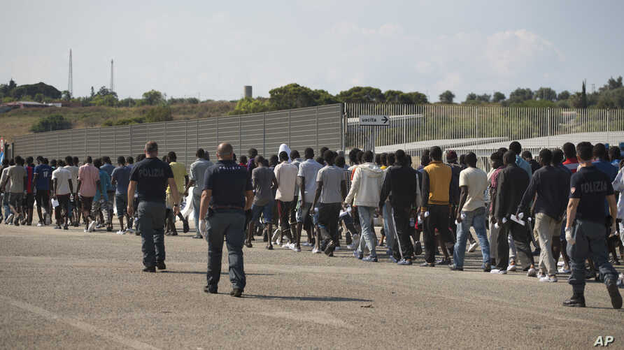 FILE - Italian border police escort sub-Saharan men on their way to a relocation center, after arriving in the Golfo Azzurro rescue vessel at the port of Augusta, in Sicily, Italy, June 23, 2017.