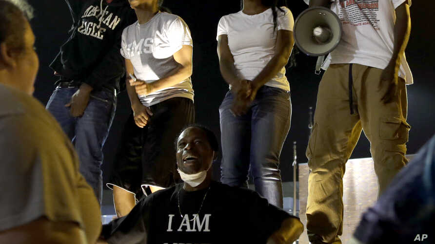 A small group of people protest outside the police station, Sept. 26, 2014, in Ferguson, Missouri.