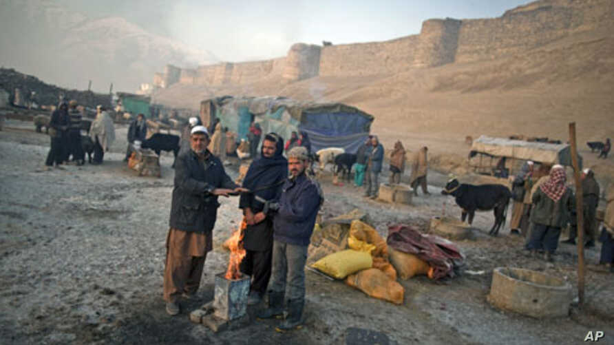 Afghan men stand next to a fire on a cold morning in an open livestock market near Bala Hissar, an old fortress, in Kabul, Afghanistan, January 10, 2012.