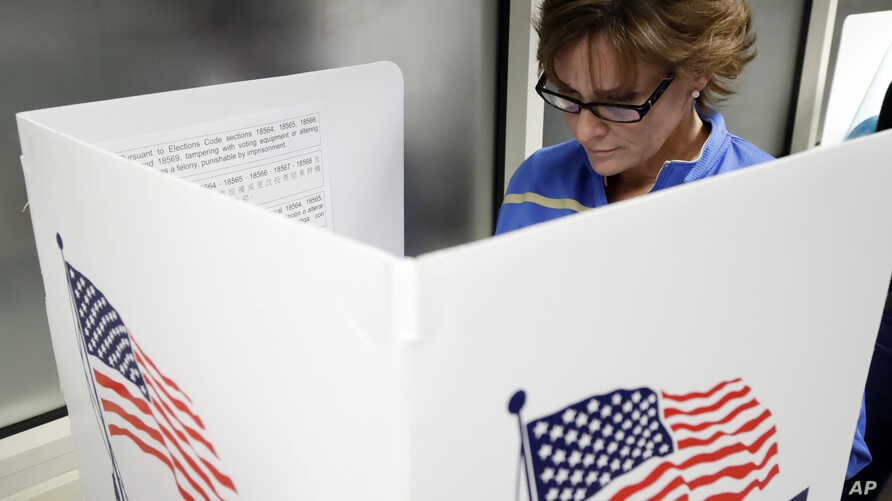 FILE - Ellen Sathe votes at Santa Clara County Registrar of Voters, Oct. 24, 2016, in San Jose, California, where  voting rights advocates say they will monitor more polling places than usual on Election Day amid concerns about possible voter intimi