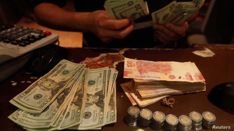 An employee counts U.S. dollar banknotes at a foreign exchange house in Ciudad Juarez, Mexico, Nov. 8, 2016. Mexico will likely raise interest rates to support its currency in the wake of the U.S. election.
