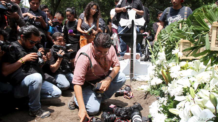A photographer places his camera next to wreaths during the funeral service of late photojournalist Ruben Espinosa, at a cemetery in Mexico City, Aug. 3, 2015.