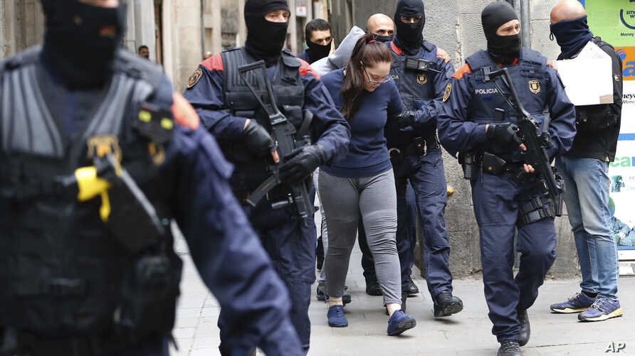 Catalan police officers detain a woman during an anti-drug trafficking operation in Barcelona downtown, Spain, Monday, Oct. 29, 2018.
