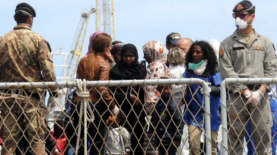 FILE - Migrants wait to disembark an Italian Navy ship in the port of Palermo, Sicily, southern Italy, May 2 2014.