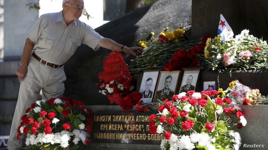 FILE - A man lays flowers during a commemoration ceremony at a monument for Kursk nuclear submarine crew in Moscow, Russia, Aug. 12, 2015.